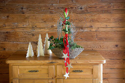Arrangement with amaryllis and stars on red ribbons on chest of drawers