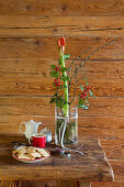 Amaryllis, branch of holly and larch twigs in glass vase