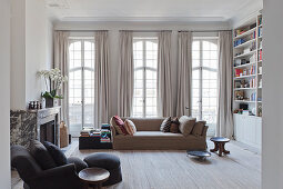 Pale sofa in front of lattice windows with floor-length curtains