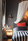 Bed with canopy in bedroom with dark grey wall