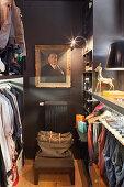 Gilt-framed portrait on dark grey wall of walk-in wardrobe