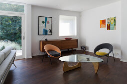 Glass-topped coffee table, two chairs and sideboard in retro interior