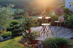 Round wooden terrace on the slope, with a patio set and roses