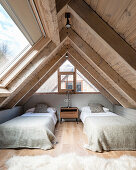 Twin beds in bedroom with wood panelling and large skylight
