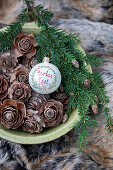 Bauble with Christmas greeting and larch cones in bowl