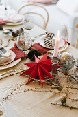 Table set for Christmas meal with red paper star, larch branches and candle