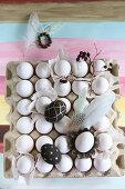 Bemalte Eier, Federn und Zweig auf einer Eierpalette mit weißen Eiern
