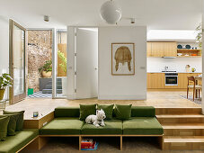 Split-level interior with built-in sofas next to steps leading to kitchen area