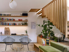 Futon sofa and wire chairs in living area with wooden staircase leading to upper storey in background