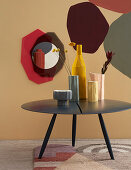 Structured vases on round coffee table in front of painted wall