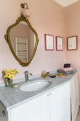 Antique gilt-framed mirror on pink wall in bathroom