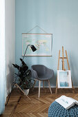 Armchair, plants and easel below map of the world on pale blue wall