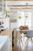 Open-plan interior with dining table and kitchen in modern country-house style