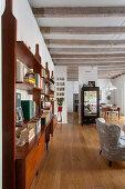 Retro-Regale im offenen Wohnraum mit Balkendecke und Holzboden