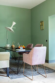 Elegant armchairs around dining table in dining area with green walls