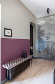 Delicate bench against wall painted in shades of grey and berry in hall