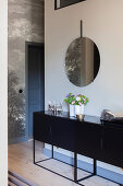 Sideboard below round mirror on wall in hall