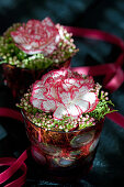 Carnation flowers with laurel viburnum buds in small jars