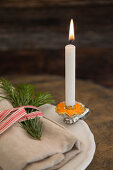 Candle in star cut out of orange peel