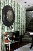 Mirrored sideboard below convex mirror on wall with botanical wallpaper