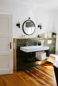 Sink with two sets of taps against green wall tiles with wooden frame
