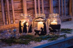 Weiße Kerzen in Einmachgläsern mit Scheerenschnitten bemalt