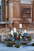 Weiße Kerzen auf Ästen mit nummerierten Täfelchen als Adventskranz