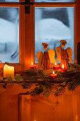 Engel aus Zimtstangen und Kerzendeko am ländlichen Fenster