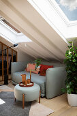 A light grey sofa and a matching coffee table in an attic room