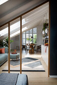 A view from a bedroom into a living room with a sofa, a kitchen and a dining area