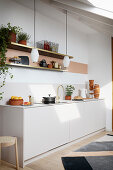A white kitchen counter with an open shelf above it and pendant lamps hanging from the ceiling