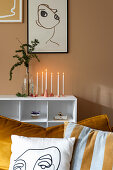 Handmade candle holders below one-line drawing on brown wall