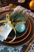 Pine twig and turquoise Christmas-tree bauble on napkin