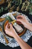 Hands tying decorations around napkin on set dining table