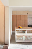 Island counter in open-plan kitchen with fitted furnishings in pale wood