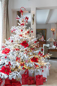 White Christmas tree decorated with poinsettias and red baubles