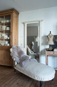 An 18th century chaise lounge in front of a wall mirror