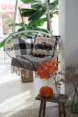 Autumnal arrangement on stool in front of hanging chair with scatter cushions
