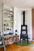 A cast iron stove, firewood and a wooden shelf in a dining room