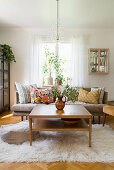 Coffee table on flokati rug and sofa with scatter cushions in living room