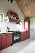 A red-brown kitchen work surface in a room with a high ceiling