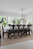 A long dining table with upholstered wooden chairs in front of the window