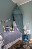 Cuddly toys on a bed with a canopy in a boy's room with a grey-blue wall