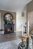 A round mirror on a taupe wall over a fireplace