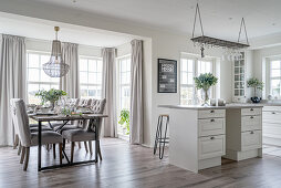 A dining area with upholstered chairs and a kitchen island in an open-plan living room