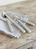 Cutlery with pale grey handles on grey napkins and rustic wooden surface