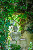 Overgrown stone wall with antique bust