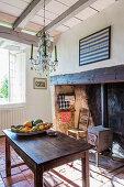 Kronleuchter über Holztisch in rustikaler Küche mit Holzofen