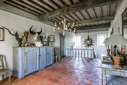 Collection of antlers and animal heads on landing with terracotta tiled floor and wood beam ceiling