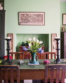Tulips and candlestick on dining table with oak chairs